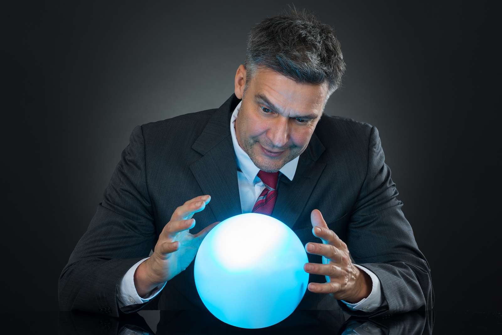 Portrait Of Businessman Predicting Future With Crystal Ball On Desk